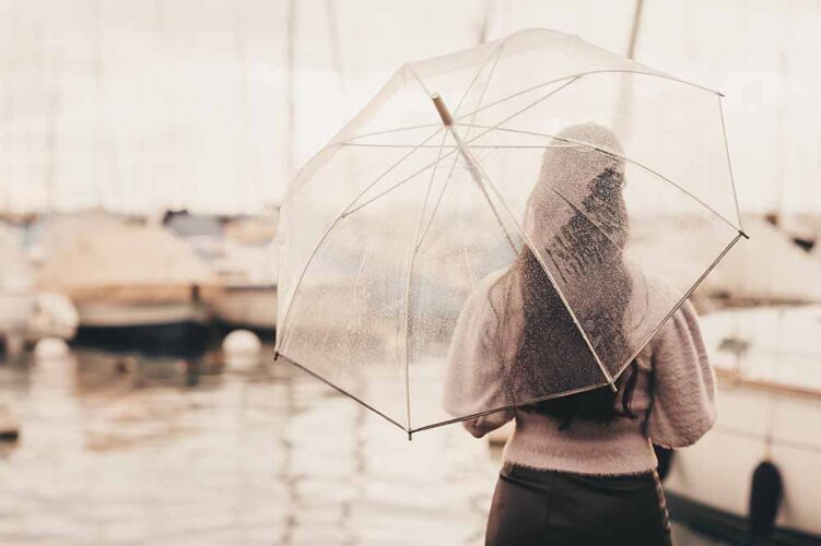 Outdoor portrait of young woman under the rain, holding umbrella, looking far away, back view, retro styled image