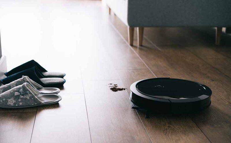 Robotic vacuum cleaner on laminate wooden floor, autonomous clea