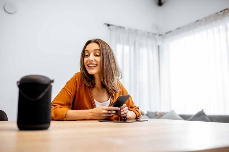 Young cheerful woman controlling home devices with a voice comma