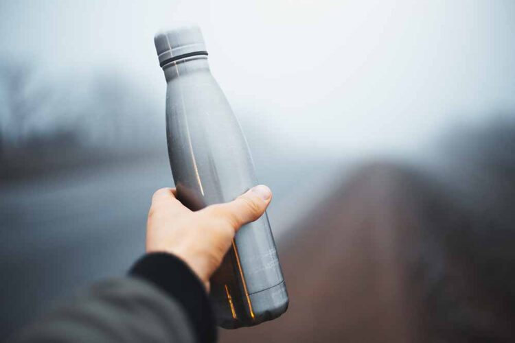 Close-up of male hand holding reusable steel thermo water bottle on background of foggy road.