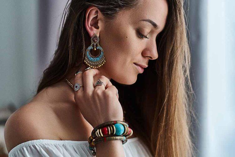 Stylish sensual brunette boho chic woman wears big earrings, bra